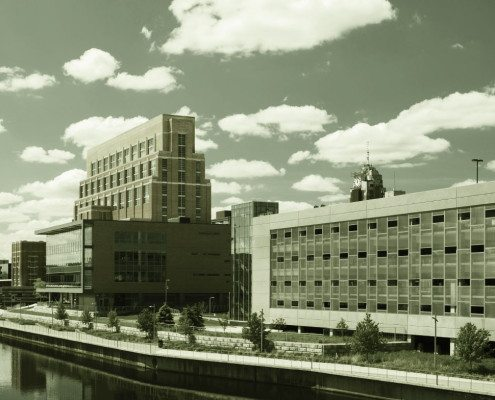 A view of Grand River in Downtown Lansing with puffy clouds in the background and a tree (for framing) in the foreground.