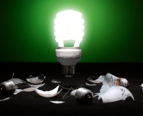 Glowing compact fluorescent light bulb hovering over the top of some broken incandescent light bulbs.  Concept for going green.