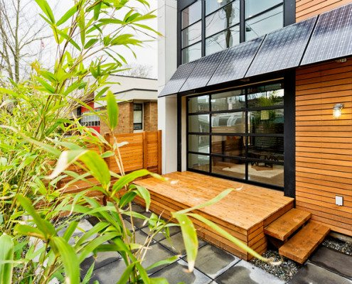 Photo of a modern home exterior with solar panel awnings.