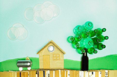 Scene of house with tree, car, clouds and fence made out of recycled materials
