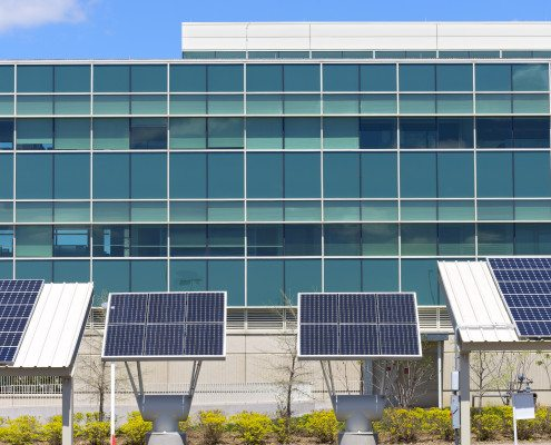 Ground level solar panel arrays in front of modern office building
